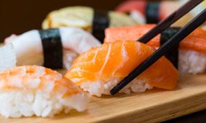 筷子夹起的三文鱼寿司摄影高清图片