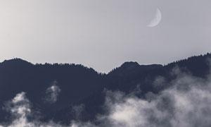 月亮与云雾笼罩的山间树林高清图片