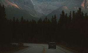 雪山与行驶在道路上的汽车高清图片