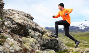 跑上小山丘的橙衣男子摄影高清图片