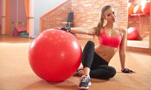 红色健身球旁的运动美女摄影高清图片
