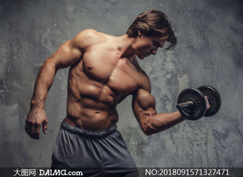 手握哑铃秀肌肉的男子摄影高清图片