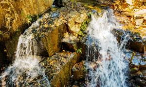 山上岩石流淌着的瀑布摄影高清图片