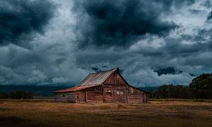 郊外黑云下的木质房子摄影高清图片