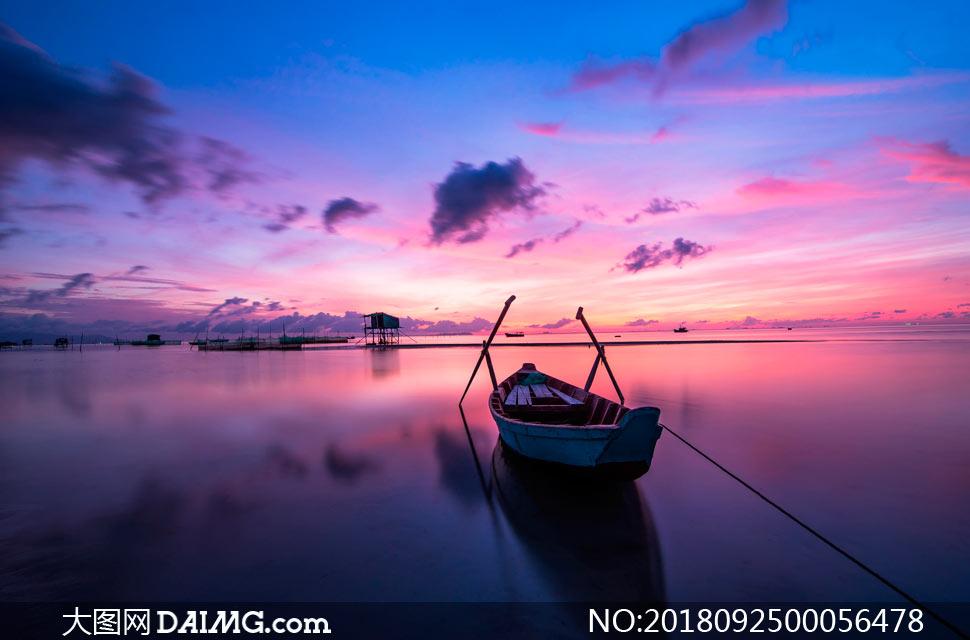夕阳下湖泊中停泊的小舟摄影图片