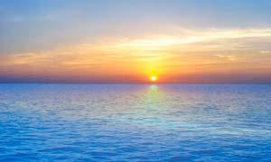 夕阳下海天一线美景摄影图片