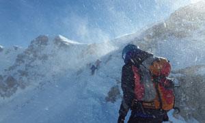 冒着风雪前行的登山者摄影高清图片