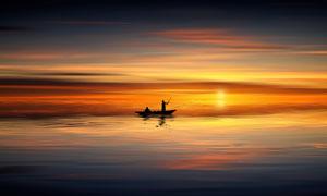 泛舟于海上的人物剪影攝影高清圖片