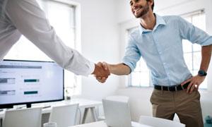 叉腰姿势与客户握手的人物高清图片