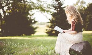 在公园看书的金发美女摄影高清图片