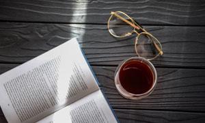 桌面上的书与茶饮眼镜摄影高清图片