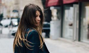 街上拎着包的长发美女摄影高清图片
