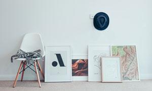 椅子与靠墙摆放的画框摄影高清图片