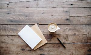 桌面上的咖啡杯与纸笔摄影高清图片
