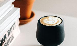 在桌面上的拉花咖啡与书籍高清图片