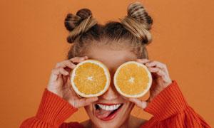 用橙子遮住双眼的俏皮美女高清图片