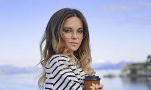 手里拿着咖啡杯的美女摄影高清图片