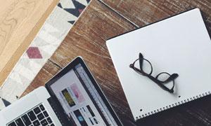 桌上的笔记本电脑与绘图本摄影图片