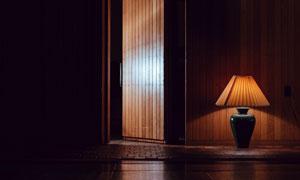 墙根台灯与开着的房门摄影高清图片