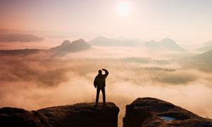 眺望云海中群山的人物剪影高清图片