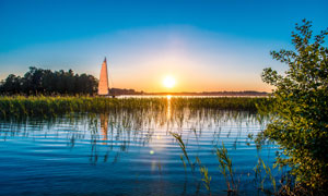 夕陽西下湖面水草帆船攝影高清圖片