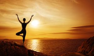 在大海邊練瑜伽的人物剪影高清圖片