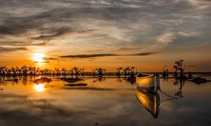 夕陽下海邊停泊的小舟攝影圖片