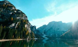 阳光下大山中的湖泊摄影图片