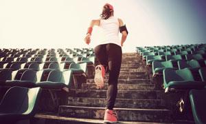 体育场馆里跑上台阶的美女高清图片