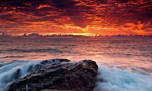 夕阳下海边海浪击打着岩石摄影图片