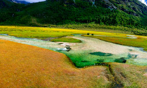 青山下的草地和溪流摄影图片