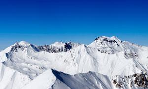 藍天下遼闊的雪山美景攝影圖片