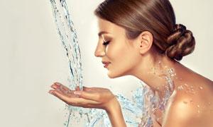 伸出手洗脸的盘发美女摄影高清图片