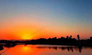 夕阳下在湖边钓鱼美景摄影图片