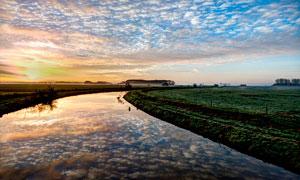 夕阳下的河流和田园风光摄影图片