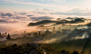 清晨山坡上云霧繚繞的村莊攝影圖片