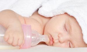 抱着空奶瓶睡觉的宝宝摄影高清图片