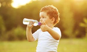 喝着水翘起拇指的儿童摄影高清图片