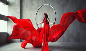 坐在吊環上的紅裙孕婦攝影高清圖片