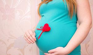 手拿著心形物件的孕婦攝影高清圖片