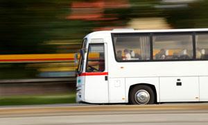 驶在道路上的客运大巴摄影高清图片