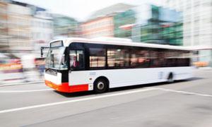 行驶在城市马路上的公交车摄影图片