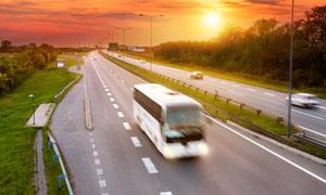 黄昏时公路上的大巴车摄影高清图片