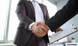 西装打扮商务人物握手手势特写高清图