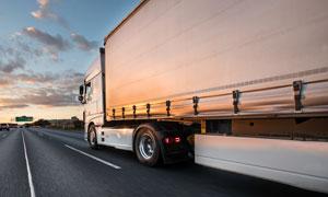 迎着夕阳行驶的集装箱卡车高清图片