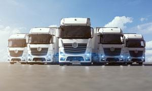 路上亮着灯的货车车队摄影高清图片