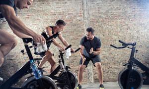 在教练指导下骑单车的男子摄影图片