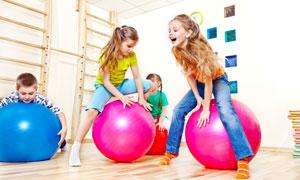 在玩着健身球的小女孩摄影高清图片