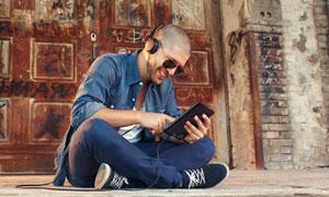 坐著玩數碼設備的男人攝影高清圖片