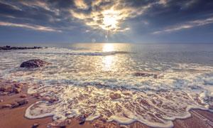 海景与乌云后面的耀眼阳光高清图片